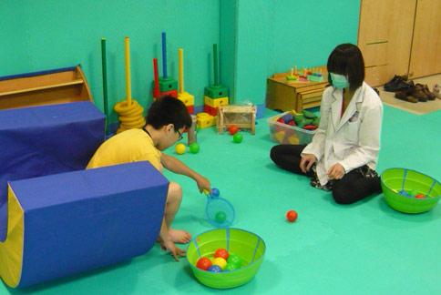 職能治療師潘介玉(右)指出,藉由遊戲訓練可幫助遲緩兒學習發展。(圖片提供/雙和醫院)