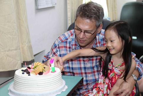 出生時體重只有800克的早產兒mimi醬(右),在養父的帶領下,回到出生醫院感謝醫護人員當年的辛勞照護。(圖片提供/彰化基督教醫院)