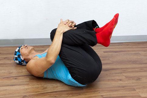 第五招:雙腿曲膝拉至胸前,將脊椎與背部伸展。(攝影/楊伯康)