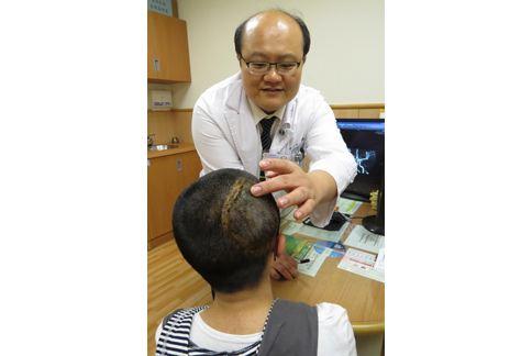 楊道杰醫師檢查郭同學術後的傷口。(圖片提供/台中慈濟醫院)