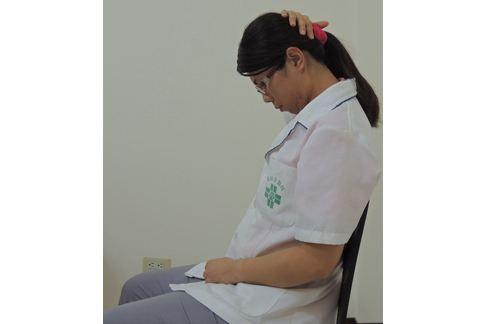 先將下巴後縮,再利用手掌由後枕部緩慢將下巴往胸口靠近。(圖片提供/童綜合醫院)